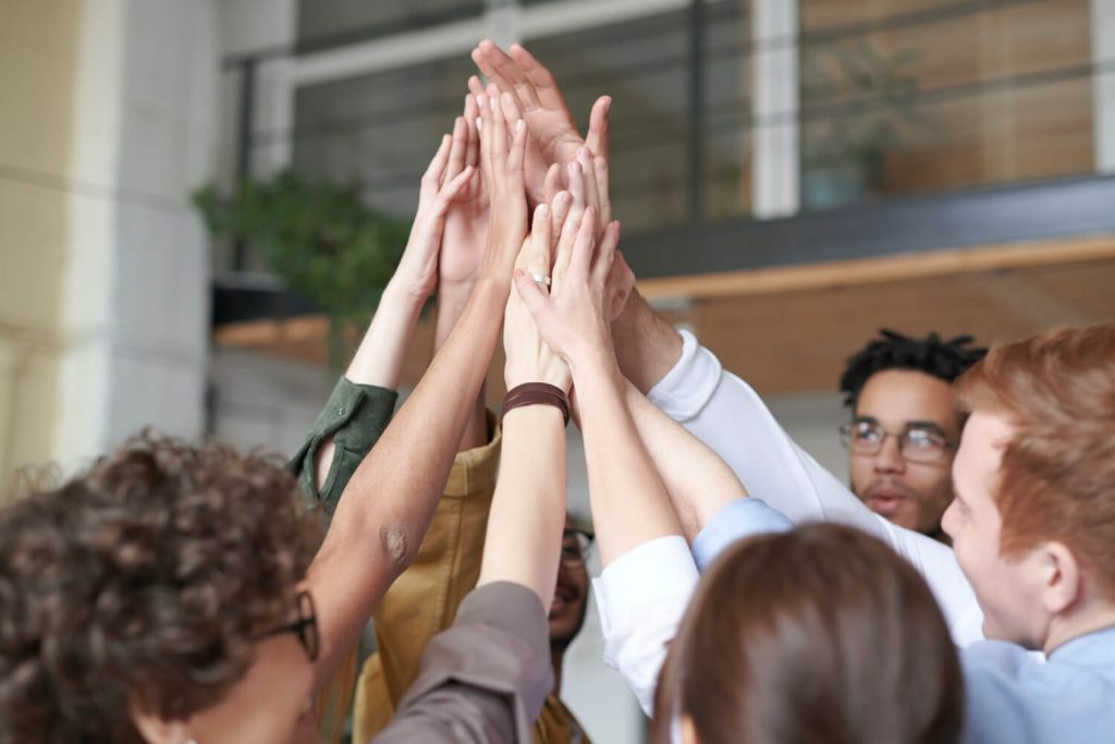 Ausgezeichnet.org talks about the relevance of good communication within the team in the context of personnel marketing, as picture shows how a team puts their hands together in the air